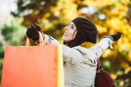 outstretching: Blissful woman holding shopping bags and having fun buying in autumn rain. Successful female shopper outside in fall season.