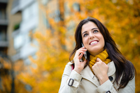 girl looking up: Happy woman on cellphone call outdoor on the street in autumn season. Happy female talking on smartphone and wearing raincoat and scarf on fall trees and city background.