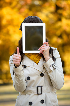 covering: Unrecognizable woman covering her face with digital tablet blank screen and doing success thumbs up gesture in autumn season outdoor. Female holding touchpad for copy space message or information.
