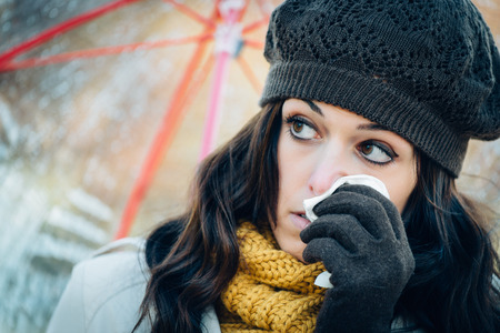 cold woman: Sad woman with cold or flu blowing her nose with a tissue under autumn rain. Brunette female sneezing and wearing warm clothes against cold weather. Illness, depression and allergy concept. Stock Photo