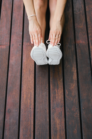 female fitness: Fitness lifestyle and sport concept. Sporty footwear and female hands close up. Woman stretching legs outdoor on wooden floor. Stock Photo