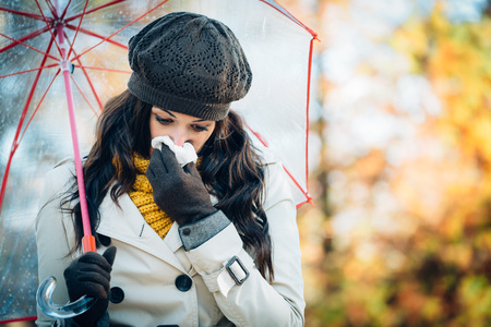 nose close up: Sad woman with cold or flu blowing her nose with a tissue under autumn rain. Brunette female sneezing and wearing warm clothes against cold weather. Illness, depression and allergy concept. Stock Photo