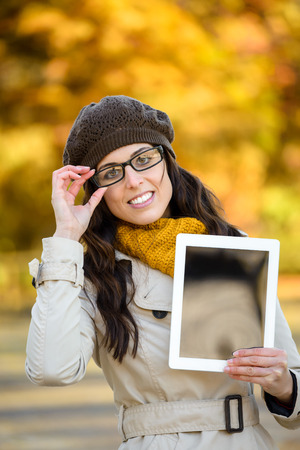 blanck: Woman with glasses showing digital tablet in autumn. Fashion brunette with eyewear showing copy space blanck frame touchpad screen.