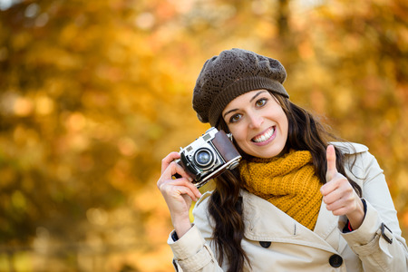 thumbs up woman: Success and happiness in autumn. Woman holding camera and doing thumbs up success gesture against fall season colors foliage background. Fashionable girl wearing scarf, raincoat and cap. Stock Photo