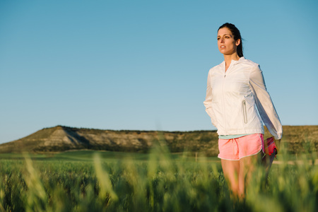 Woman warming up and stretching legs before running at country rural path surrounded by field. Outdoor exercising and training. photo