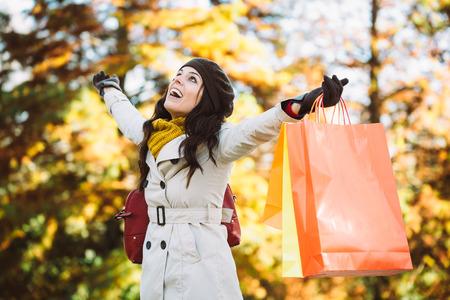 compras: Mujer dichosa celebraci�n de bolsas de la compra y que tiene la compra de diversi�n en la lluvia de oto�o. Comprador femenino �xito fuera de la temporada de oto�o. Foto de archivo