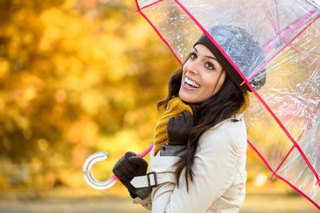 Donna allegra con l'ombrello sotto la pioggia autunnale stagione indossa vestiti caldi di moda.