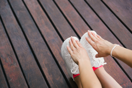 shoes woman: Fitness lifestyle and sport concept. Sporty footwear and female hands close up. Woman stretching legs outdoor on wooden floor. Stock Photo