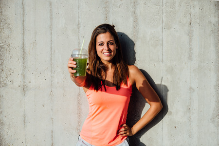 green vegetables: Sporty woman offering detox green smoothie. Happy sportswoman showing healthy fruit and vegetables drink. Fitness lifestyle and nutrition concept.
