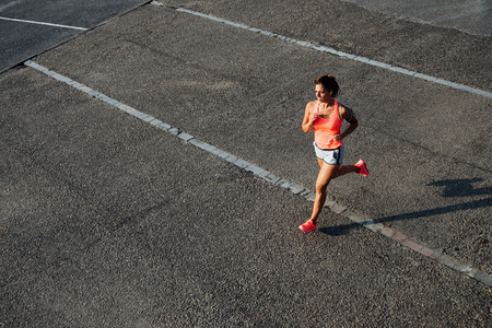 armband: Top view of woman running on city asphalt. Female runner training outdoor.