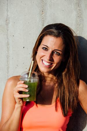 tomando jugo: Mujer deportiva que sostiene desintoxicación batido verde. Feliz deportista con la bebida saludable de frutas y hortalizas. estilo de vida saludable y el concepto de nutrición.