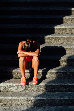 Frustrated sporty woman suffering overtraining. Sport and fitness despair and frustration concept.