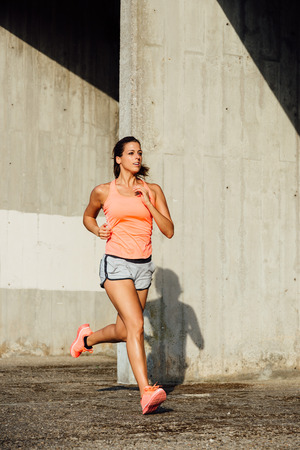 Sporty cheerful woman running and training outdoor. Female runner exercising.