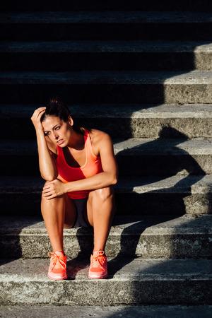 deportistas: Mujer deportiva sobreentrenamiento sufrimiento frustrado y cansado. Deporte y aptitud desesperación y frustración concepto. Foto de archivo