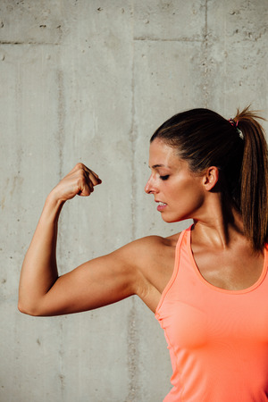 woman muscle: Strong fit woman flexing arm biceps. Fitness workout and motivation concept.