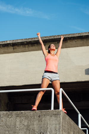 arms up: Sporty woman celebrating workout success and achievements. Successful happy athlete raising arms. Stock Photo