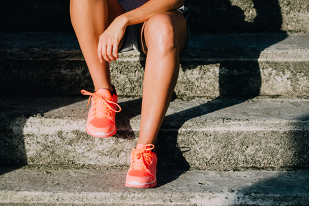 rest: Woman taking a workout rest. Sporty and running footwear close up. Fitness motivation and healthy lifestyle concept. Stock Photo