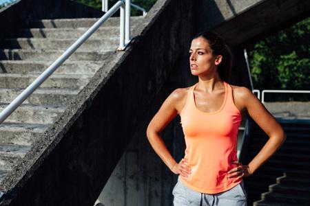escalera: Mujer sudoración atleta después de subir escaleras, correr y hacer ejercicio al aire libre. Mujer sudorosa deportivo de tomar un descanso del entrenamiento de fitness.