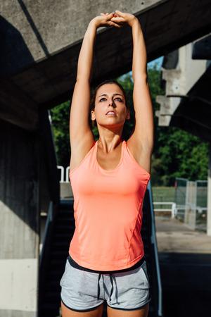 elasticidad: Mujer que estira los brazos Sporty. Atleta femenina de entrenamiento de fitness al aire libre. Foto de archivo