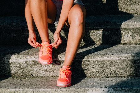 Woman lacing running and sport shoes. Sporty footwear close up. Fitness motivation and healthy lifestyle concept. Banque d'images