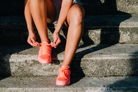 mujer sentada: Mujer que ata el funcionamiento y zapatos de deporte. Calzado deportivo cerca. Gimnasio motivación y concepto de estilo de vida saludable. Foto de archivo