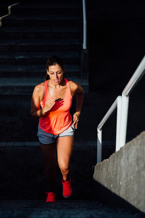 stairs: Female athlete running and climbing stairs for power legs training. Sporty woman exercising outdoor. Stock Photo