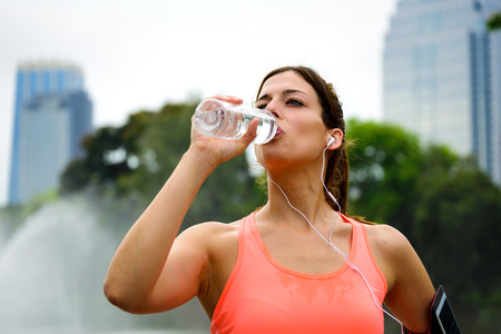 hydration: Fitness woman drinking water from bottle during running or outdoor workout rest at city park. Female athlete taking a break for hydration.