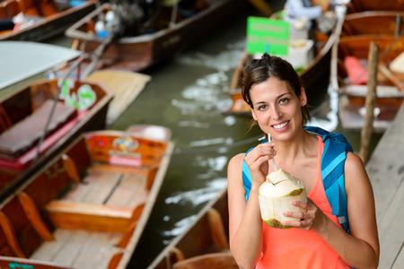damnoen saduak: Happy female tourist visiting Damnoen Saduak floating market at Bangkok, Thailand. Woman on Asian travel drinking fresh coconut water.