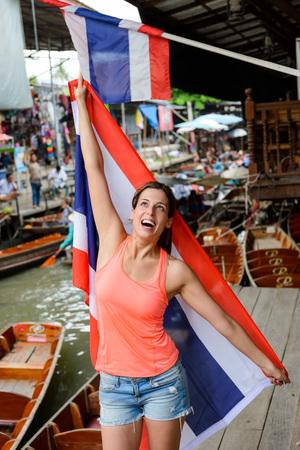 damnoen saduak: Joyful woman having fun at Damnoen Saduak floating market showing Thailand flag at Bangkok. Female tourist on Asia Travel.