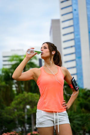 hydration: Fitness woman drinking water after outdoor workout at city park. Female athlete taking a training rest for hydration.