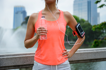 Sweaty woman drinking water during outdoor fitness workout rest. Female runner taking a running break. Standard-Bild