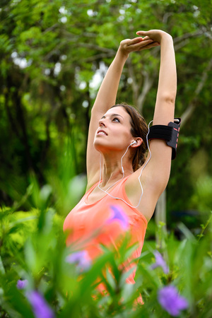 warming up: Woman doing stretching arms for relaxing exercise or warming up before outdoor workout at city park on spring. Stock Photo