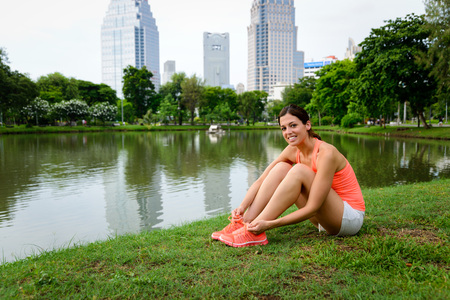 lacing: Female athlete preparing for running. Sporty woman lacing sport shoes before outdoor fitness workout and exercising. Lumpini Park, Bangkok.