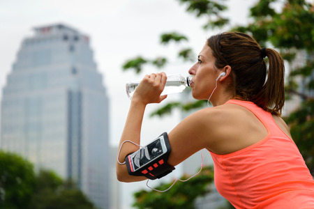 hydration: Fitness woman drinking water from bottle during running or workout rest at city park. Female athlete taking a break for hydration. Stock Photo