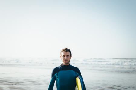 Male surfer beach lifestyle portrait. Man in wetsuit with bodyboard surfing equipment.