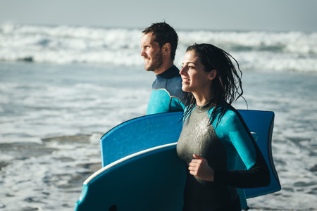bodyboarding: Young couple of bodyboard surfers runnign. Surfing and outdoor sport lifestyle concept. Woman and man after bodyboarding.