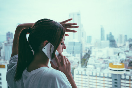Sad woman on cellphone call looking through the window at grey rainy city. Heartbreak and couple problems concept.