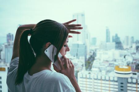person calling: Mujer triste en la llamada tel�fono celular que mira a trav�s de la ventana en la ciudad gris y lluvioso. Angustia y problemas de los pares concepto.