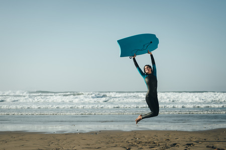 wetsuit: Woman in wetsuit with bodyboard surfing equipment having fun at the beach. Happy female surfer jumping for celebrating success and freedom.