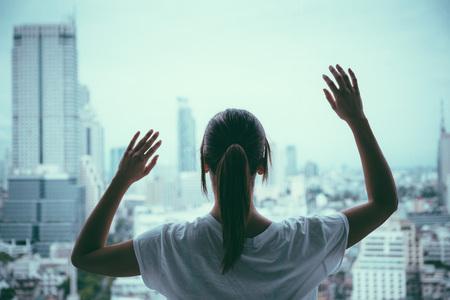 mujeres: Mujer triste mirando a trav�s de la ventana en ciudad lluviosa gris que parece presionada. La depresi�n, problemas y concepto de la soledad. Foto de archivo