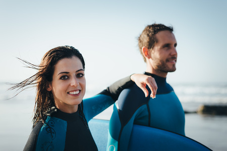 bodyboarding: Young couple of bodyboard surfers. Surfing and outdoor sport lifestyle concept. Woman and man after bodyboarding. Stock Photo