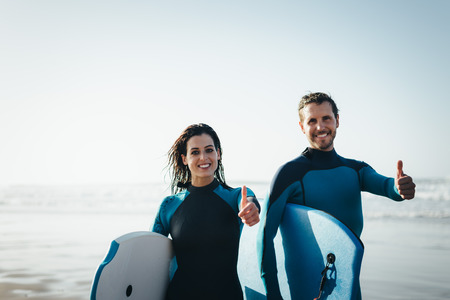 bodyboarding: Successful couple of surfers. Surfing and outdoor sport lifestyle concept. Woman and man after bodyboarding.