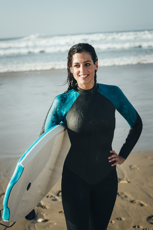 wet suit: Female surfer beach lifestyle portrait. Woman in wetsuit with bodyboard surfing equipment.