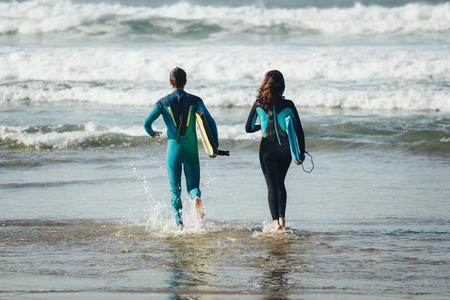 bodyboarding: Back view of Young couple of bodyboard surfers running. Surfing and outdoor sport lifestyle concept. Woman and man after bodyboarding.