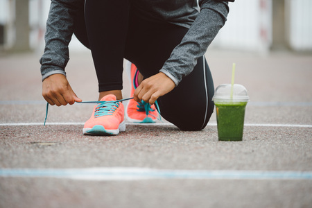 challenging: Fitness workout and healthy nutrition concept.  Detox smoothie drink and running footwear close up. Female athlete tying sport shoes laces before training outdoor.
