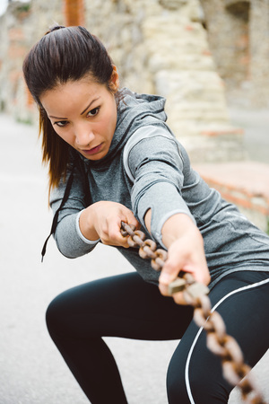 Fitness woman training strength. Pull exercise workout outdoor with chain.