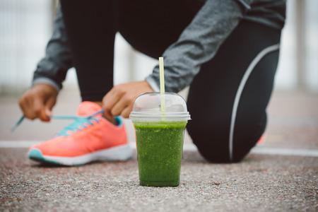 fitness: bebida batido de desintoxicación y calzado corriendo cerca. Ciudad de entrenamiento al aire libre y gimnasio concepto de nutrición saludable. Atleta femenina que ata los zapatos de deporte cordones antes de entrenar.