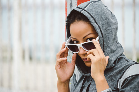 tough woman: Tough looking urban fitness woman portrait. Sporty ethnic athlete wearing sunglasses and hood for outdoor workout.