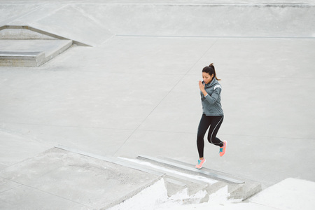 workout: Urban fitness woman running and climbing staris for legs power and strength training. Female athlete working out outdoor.
