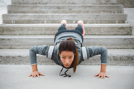 Urban fitness woman workout doing feet elevated push ups on urban park stairs. Motivated female athlete training hard. Stock Photo